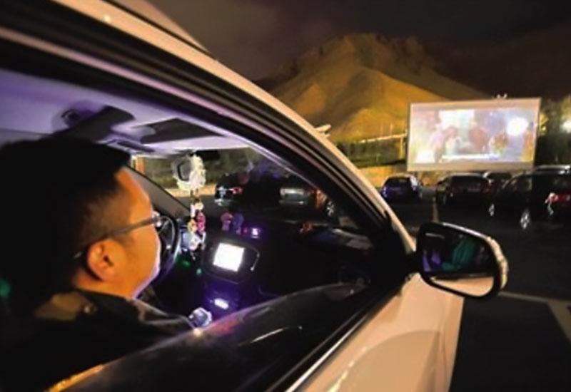 西藏汽车电影院一名观众在汽车内观影的照片